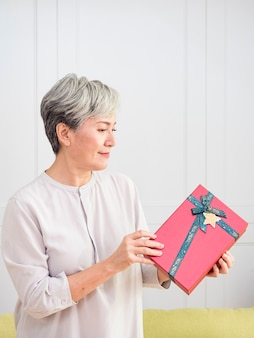 Portret starszej azjatki otrzymuje pudełko na prezent