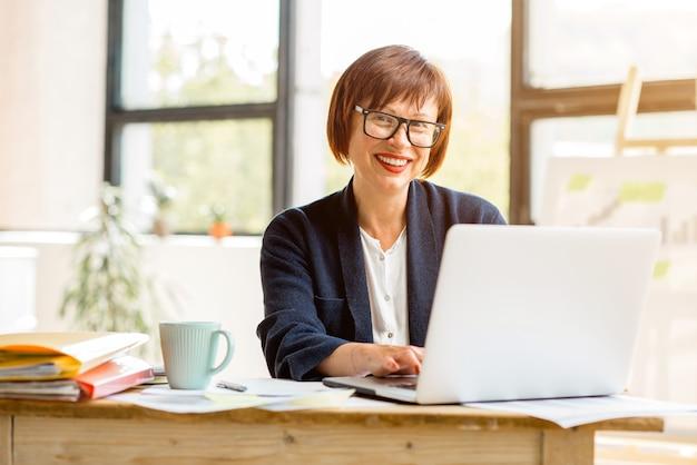 Portret starszej bizneswoman pracującej z dokumentami i laptopem w jasnym, nowoczesnym wnętrzu biurowym