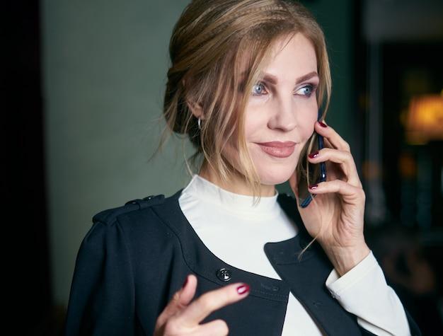 Portret starszej kobiety biznesu noszenie formalnego koloru rozmawia przez telefon