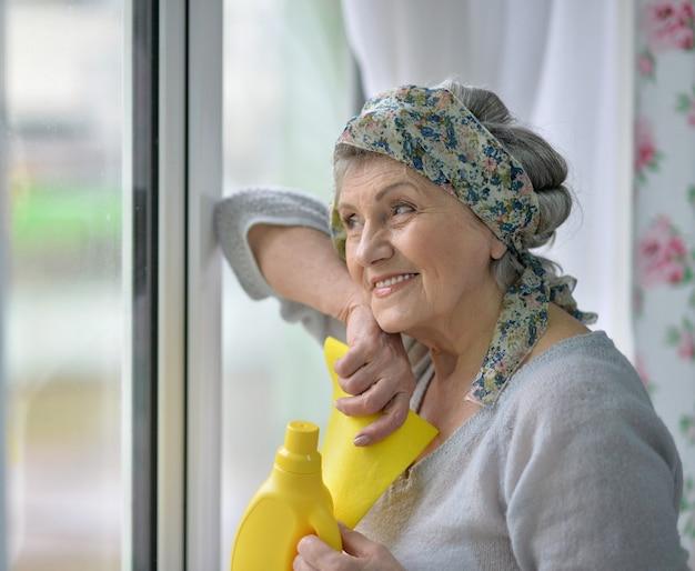 Portret starszej kobiety myjącej okno w domu