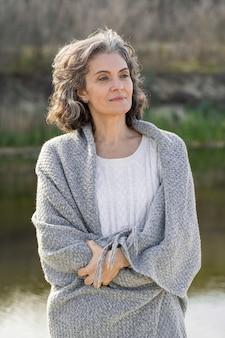 Portret starszej kobiety na zewnątrz nad jeziorem