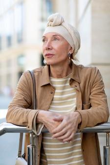 Portret starszej kobiety na zewnątrz w mieście