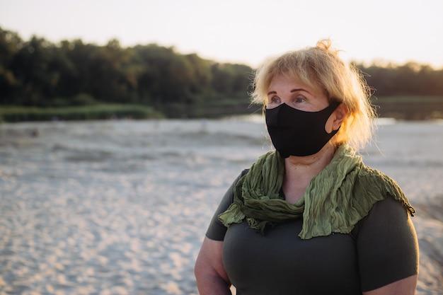 Portret starszej kobiety noszenia maski medycznej. koncepcja koronawirusa. ochrona dróg oddechowych