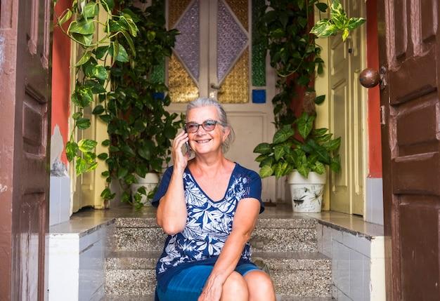 Portret starszej kobiety o białych włosach rozmawiającej ze smartfonem, siedząc na schodach