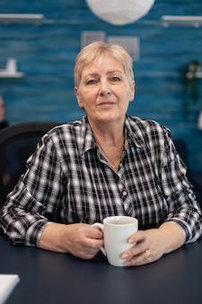 Portret starszej kobiety patrzącej na kamerę podczas picia kubka kawy