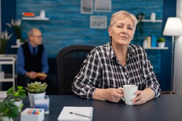 Portret starszej kobiety patrzącej w kamerę podczas delektowania się kawą zdrowa szczęśliwa starsza kobieta...