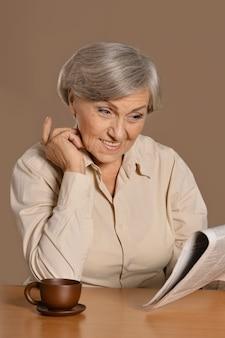 Portret starszej kobiety pijącej kawę na brązowym tle