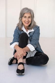 Portret starszej kobiety pozującej w dżinsowej kurtce
