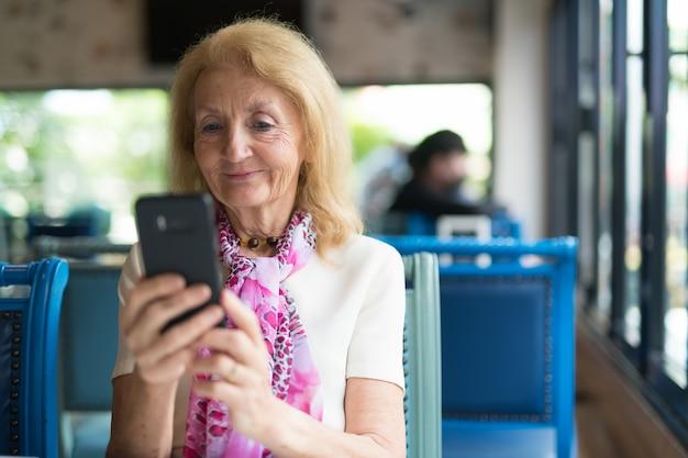 Portret starszej kobiety przy użyciu telefonu komórkowego