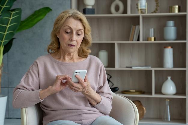 Portret starszej kobiety siedzącej na krześle w domu i korzystającej ze smartfona