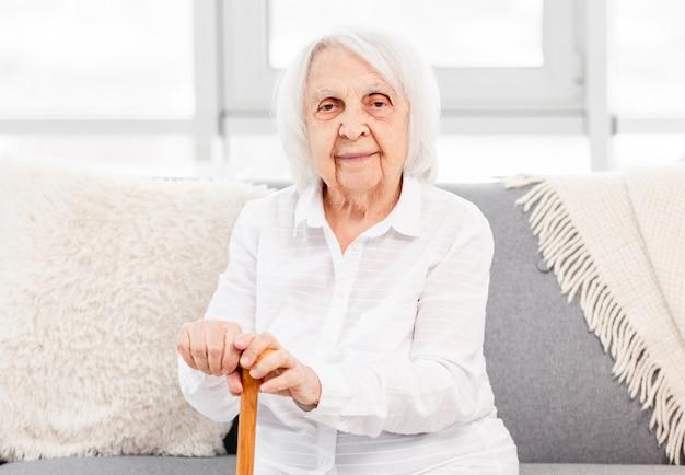 Portret starszej kobiety siwych włosów siedzi w domu i trzymając różdżkę i patrząc w kamerę