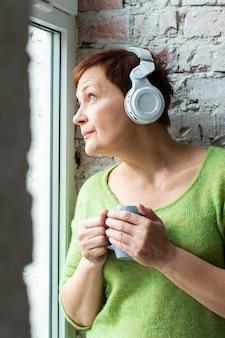 Portret starszej kobiety słuchająca muzyka i patrzeć daleko od