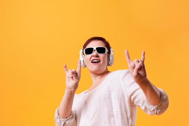 Portret starszej kobiety słuchająca muzyka rockowa