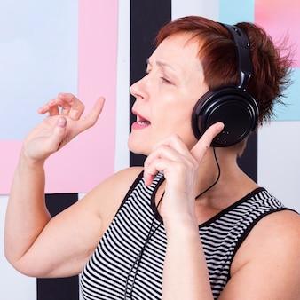 Portret starszej kobiety słuchająca muzyka