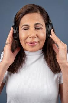 Portret starszej kobiety słuchającej muzyki przez słuchawki
