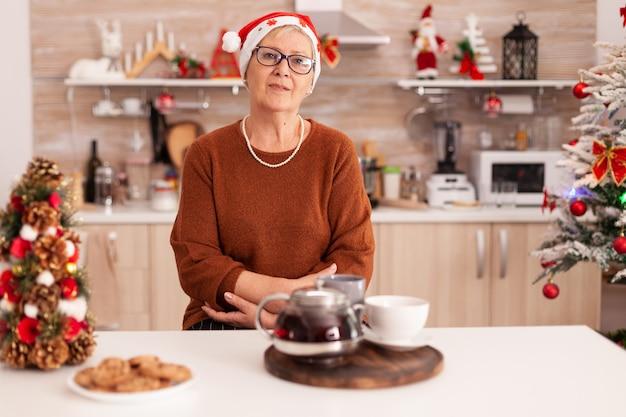 Portret starszej kobiety w kapeluszu świętego mikołaja stojącego przy stole w świątecznej udekorowanej kuchni