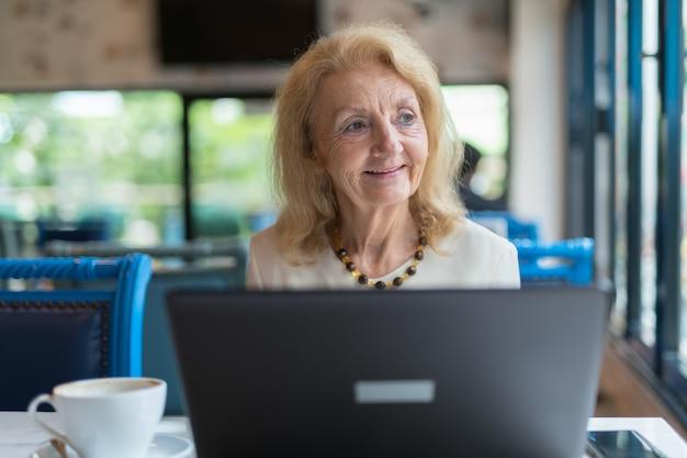 Portret starszej kobiety w podeszłym wieku siedzi i przy użyciu komputera przenośnego