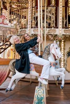 Portret starszej kobiety z córką spędzającą razem miło czas w parku rozrywki