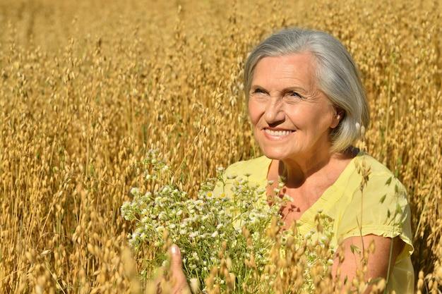 Portret starszej kobiety z kwiatami w polu