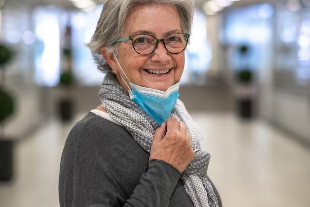 Portret starszej kobiety zdejmującej maskę chirurgiczną z powodu koronawirusa stojącego w opuszczonym centrum handlowym. atrakcyjna uśmiechnięta starsza kobieta w okularach