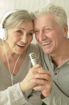 Portret starszej pary ze słuchawkami i mikrofonem