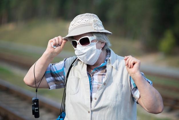 Portret starszej starszej kobiety z maską medyczną na twarzy, kapeluszu, okularach przeciwsłonecznych i aparacie fotograficznym