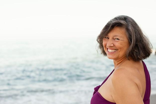 Portret starszej uśmiechniętej kobiety na plaży