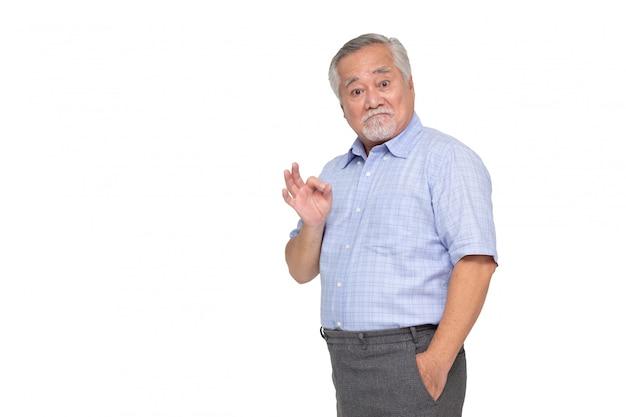 Portret starszy azjatykci mężczyzna pokazuje ok znaka odizolowywającego nad biel ścianą