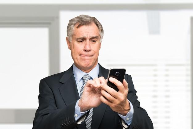 Portret starszy biznesmen używa jego telefon komórkowego w biurze