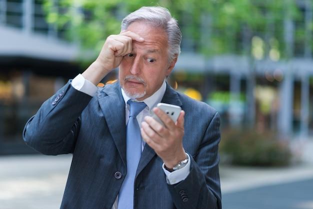 Portret starszy biznesmen używa jego telefon komórkowego