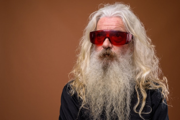 Portret starszy brodaty mężczyzna w czerwonych okularach i myślenia