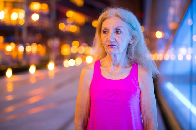Portret starszy kobieta myśli na zewnątrz w nocy