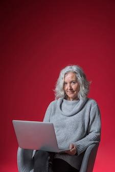 Portret starszy kobieta siedzi na fotelu z laptopem patrząc na kamery na czerwonym tle