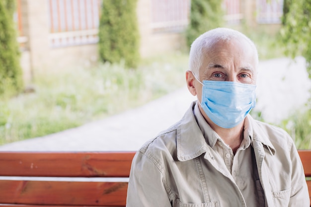 Portret starszy mężczyzna jest ubranym medyczną maskę. koncepcja koronawirusa. ochrona dróg oddechowych