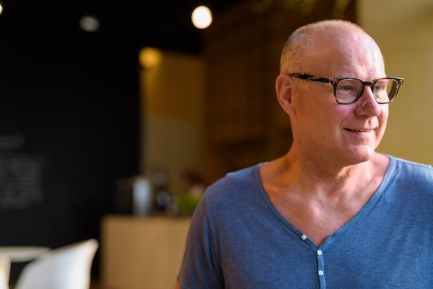 Portret starszy mężczyzna przystojny skandynawski turysta relaks w kawiarni
