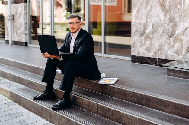 Portret starszy mężczyzna siedzi otwartego laptop na zewnątrz i trzyma w kostiumu.