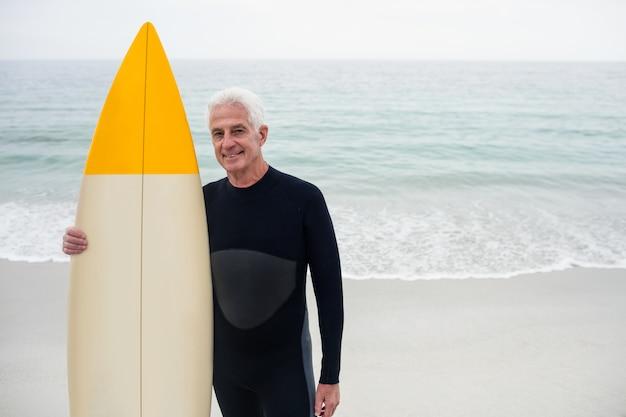 Portret starszy mężczyzna trzyma surfboard w kombinezonie