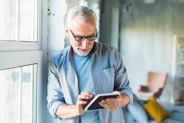 Portret starszy mężczyzna używa cyfrową pastylkę