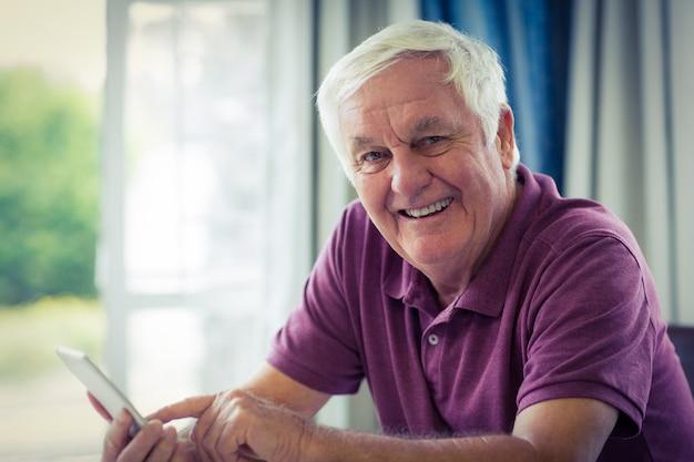 Portret starszy mężczyzna używa telefon komórkowego w domu