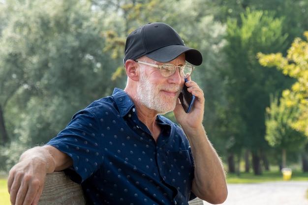 Portret starszy mężczyzna z brodą i szkłami używać smartphone