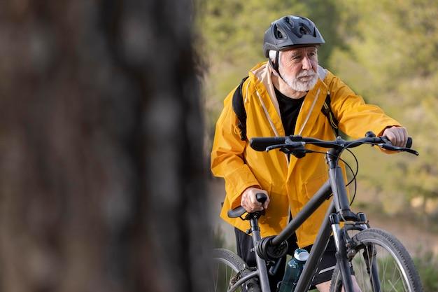 Portret starszy mężczyzna z rowerem na górze