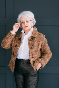 Portret starszy stylista mody. osobisty doradca ds. modnej garderoby. przekonana, starsza pani pozowanie z ręką w okularach.
