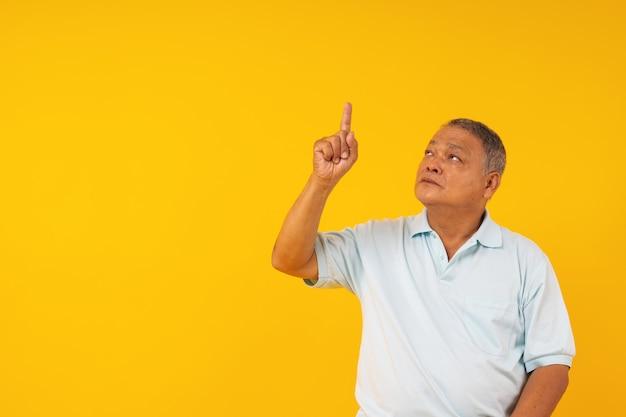 Portret stary człowiek wskazuje up na żółtym copyspace, przedstawia produkt spożywczy na copyspace i przedstawia główkowanie