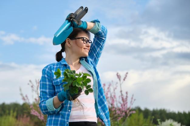 Portret starzejąca się kobieta w ogródzie z narzędziami, truskawkowi krzaki