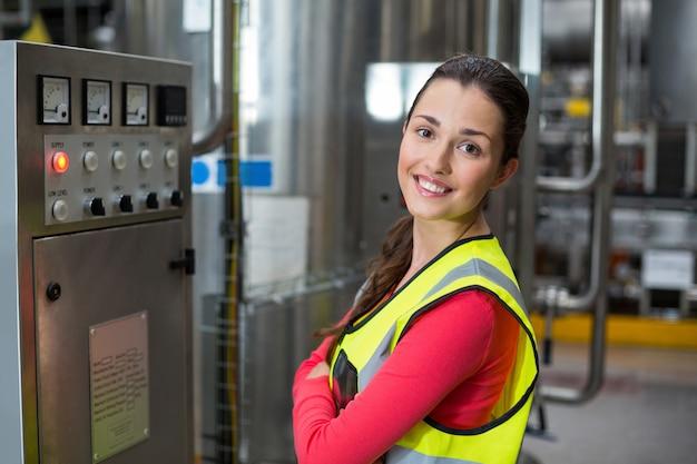 Portret stoi blisko maszyny żeński pracownik fabryczny