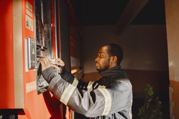 Portret strażaka stojącego przed wozem strażackim