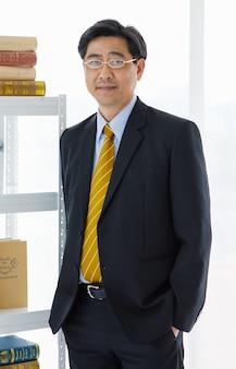 Portret strzał azjatycki starszy stary sukces firmy przedsiębiorcy w formalnym garniturze z brązowym krawatem i złotymi okularami stojących na białym tle.