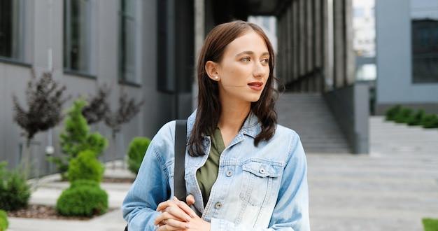 Portret strzał caucasion całkiem młoda ładna kobieta w niebieskiej kurtce dżinsowej z torbą stojącą na ulicy miasta i uśmiechając się radośnie do kamery. piękna szczęśliwa wesoła kobieta na zewnątrz.