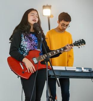 Portret strzał młodej nastoletniej piosenkarki śpiewającej piosenkę z mikrofonem i grającej na gitarze elektrycznej. profesjonalny młodszy wokalista ćwiczący z męskim pianistą w tle.