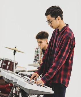 Portret strzał nastoletniego muzyka grającego na klawiaturze. selektywne skupienie na klawiszowcu z perkusistą w tle. profesjonalny młodszy uczeń grający na instrumencie jako hobby z przyjaciółmi